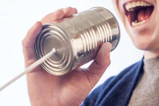Mann spricht in Dosentelefon